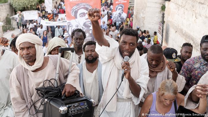 Filmstill aus Das neue Evangelium: Yvan Sagnet führt als Jesus mit Mikrofon und Verstärker Aktivistinnen und Aktivisten an