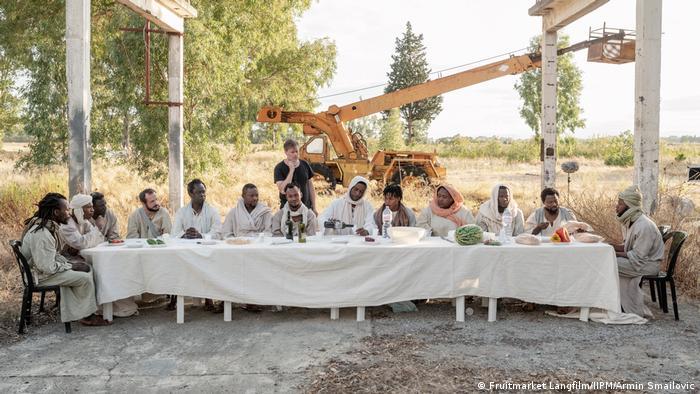 Filmstill aus Das neue Evangelium: eine lange Tafel mit Plastikstühlen, daran sitzen 13 kostümierte Schauspieler, in der Mitte Yvan Sagnet als Jesus, dahinter stehend Regisseur Milo Rau