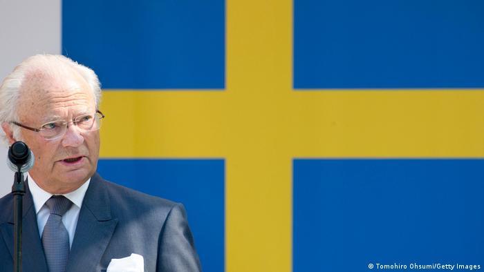 Schwedens König Carl XVI. Gustaf vor der Landesflagge