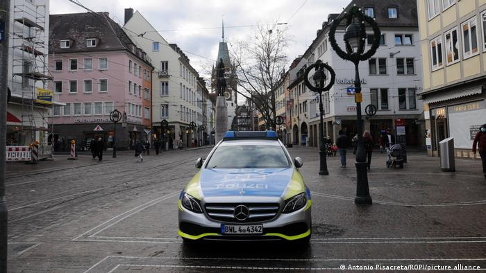 A police car stands in a near deserted petedestrian area in Freiburg