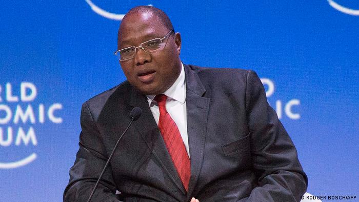 Ambrose Dlamini, de terno escuro e gravata vermelha, fala ao microfone.