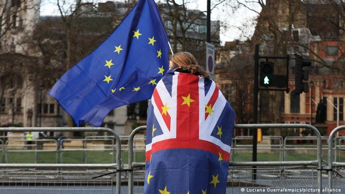 A person holding an EU flag with a British and EU combined flag around her shoulders