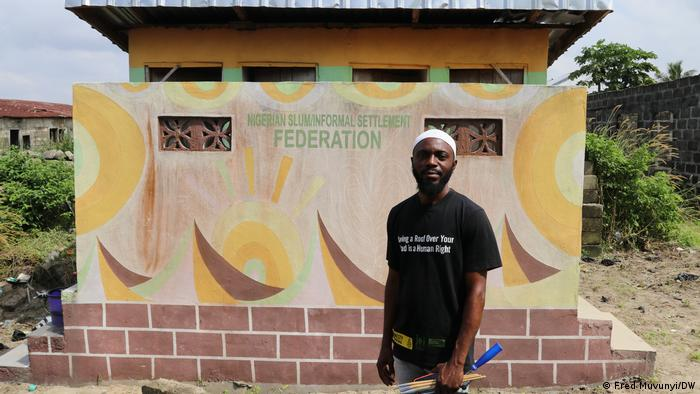 Artist Gani Taiwo in front of a bio-fill toilet designed by him