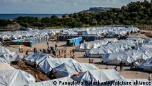 Migrants fill water as others clean their belongings after a rainstorm at the Kara Tepe refugee camp, on the northeastern Aegean island of Lesbos, Greece, Wednesday, Oct. 14, 2020. Around 7,600 refugees and migrants have settled at the new tent city after successive fires on Sept. 9, devastated the Moria refugee camp, making thousands of inhabitants homeless during a COVD-19 lockdown. (AP Photo/Panagiotis Balaskas)