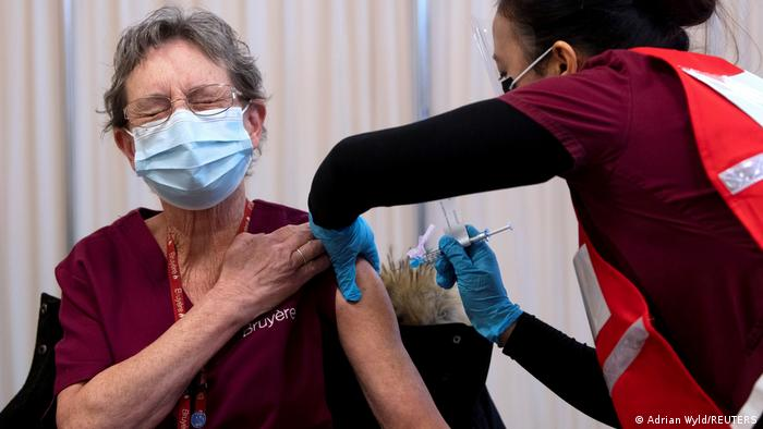 Personal support worker Johanne Lamesse reacts in anticipation to the needle as she receives the Pfizer-BioNTech COVID-19 vaccine at the Civic Hospital in Ottawa, Ontario, Canada
