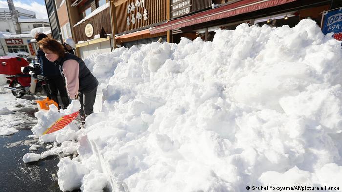 A Japanese woman shovels snow