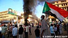 A Sudanese man wearing a face mask waves his country's national flag during protests in the capital Khartoum to mark the second anniversary of the start of a revolt that toppled the previous government, on December 19, 2020. - Frustrated by the lack of change in their daily lives, thousands of demonstrators, mostly young, marched in several towns in Sudan. (Photo by ASHRAF SHAZLY / AFP)