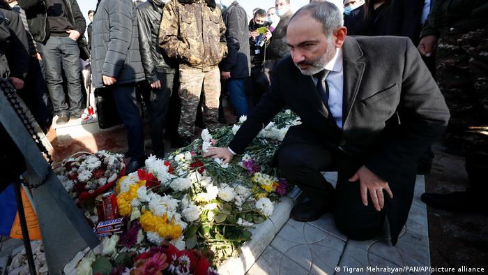 Armenian Prime Minister Nikol Pashinyan kneels at a grave covered in flowers