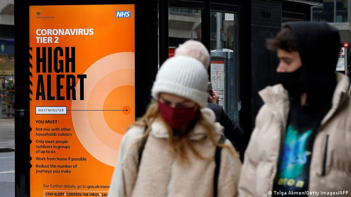 Man and woman walk on a London street with a sign reading High Alert