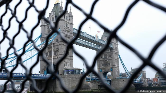 The Tower Bridge in London seen through a wire link fence