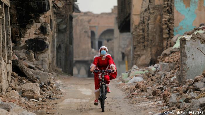 Ulice Mosula, velikog grada u Iraku, jedva da su raskrčene toliko da na biciklu može da prođe ova dama u kostimu Deda Mraza. Ostaci rata na mestu koje je do pre par godina terorisala Islamska država, a sada se bori sa koronom. Pre nekoliko dana je Irak zvanično proglasio hrišćansku proslavu Božića državnim praznikom.