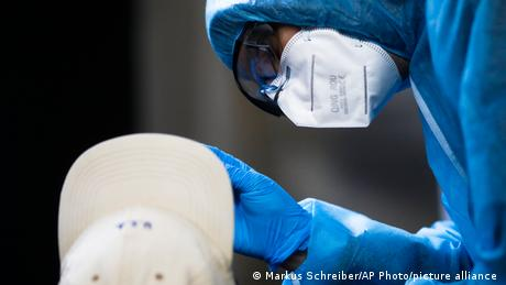 A nose swab is taken from a man for a SARS CoV-2 rapid test at the Corona Antigen Rapid test center in Berlin