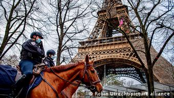 Полицейские в масках на лошадях и Эйфелева башня в Париже