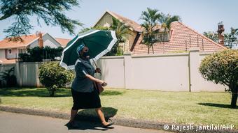 Женщина в маске под зонтиком идет по улице Дурбана