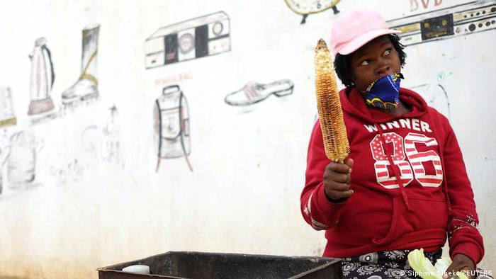 Eine Frau verkauft geröstete Maiskolben, die Maske bedeckt nur den Mund