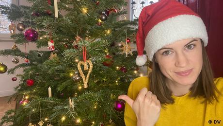 Rachel Stewart in Santa hat in front of tree