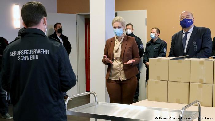 وظیفه تهیه واکسن بر عهده دولت فدرال آلمان است. آماده سازی مراکز واکسیناسیون اما بر عهده دولتهای ایالتی است. تصویری از بازدید مانوئلا اشوزیک، نخست وزیر سوسیال دمکرات ایالت مکلنبورگ فورپومرن از مرکز واکسنیاسیون در شهر شورین. او خود به تازگی از بیماری سرطان پستان بهبود یافته و بر سر کار بازگشته است.