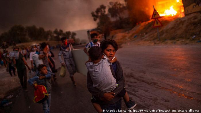 Kinder rennen auf dem UNICEF-Foto des Jahres 2020 von Angelos Tzortzinis eine Straße entlang, hinter ihnen brennt das Flüchtlingslager Moria