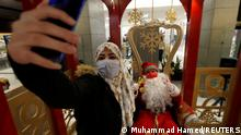 A young woman takes a selfie with a man dressed as a Santa Claus ahead of Christmas at a mall, amid fears over rising numbers of coronavirus disease (COVID-19) cases in Amman, Jordan December 15, 2020. REUTERS/Muhammad Hamed