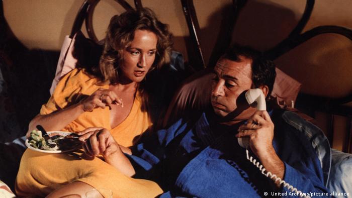 Filmstill aus La Boum: Brigitte Fossey und Claude Brasseur liegen nebeneinander im Bett, er telefoniert