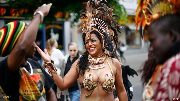 A samba dancer jokes with spectators prior to the parade at the Carnival Of Cultures in Berlin 2010 (AP)