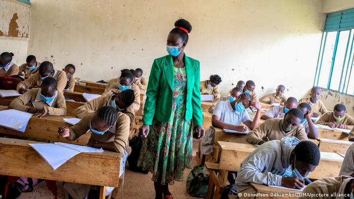 A teacher wearing a mask observes students in class wearing masks too.