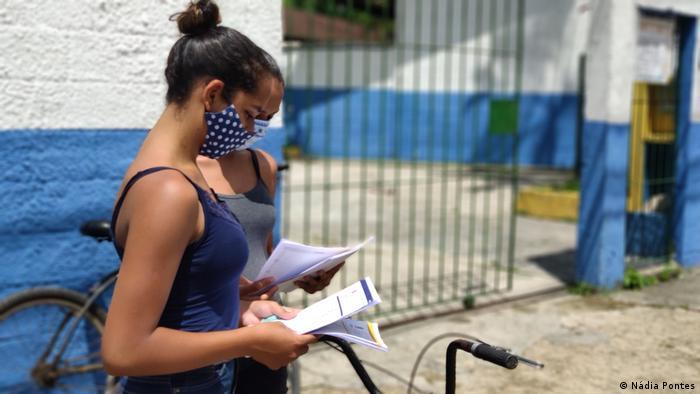 Meninas de máscara diante de escola