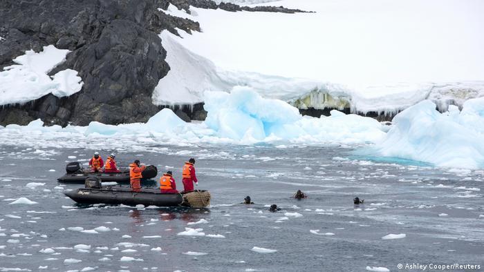 Taucher und Forscher auf Schlauchbooten vor der Küste der Antarktis