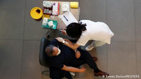 A medical worker vaccinates a man against the coronavirus disease (COVID-19) as Israel kicks off a coronavirus vaccination drive, at Tel Aviv Sourasky Medical Center (Ichilov Hospital) in Tel Aviv, Israel