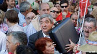 A man walks through a protest against austerity measures in Spain