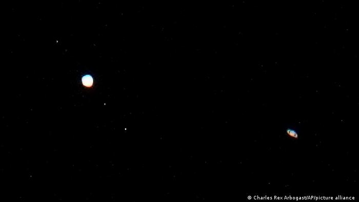 Jupiter, and three of its moons, left, and Saturn, right, are seen in the sky
