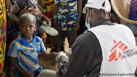 A child in Mali receives a rapid malaria test from a Doctors Without Borders worker