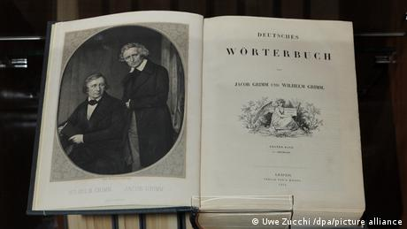 A book opened with two men pictured on the left