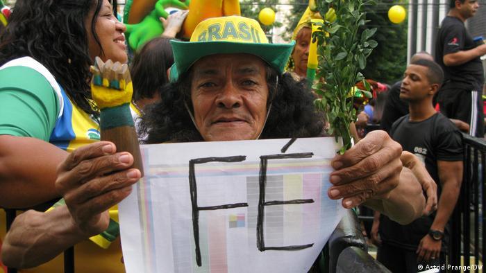 Torcedor com chapéu do Brasil segura cartaz com a palavra fé