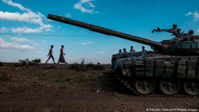 Youngsters walk next to an abandoned tank belonging to Tigrayan forces south of the town of Mehoni, Ethiopia