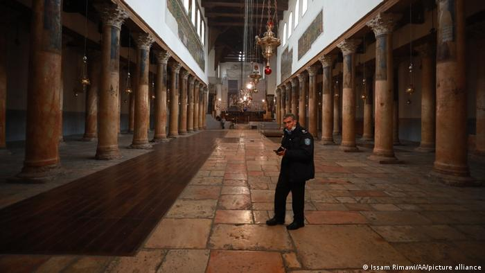 A security guard stands alone in the Church of the Nativity