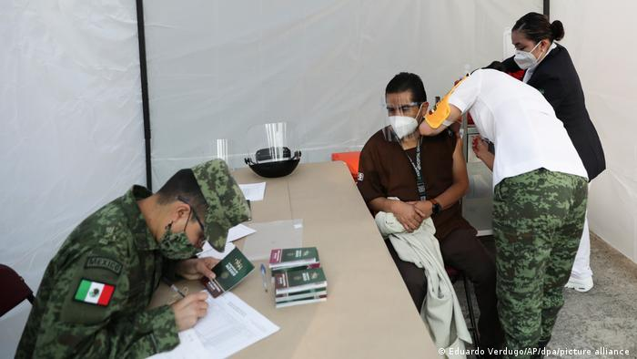 Troops carrying out COVID vaccination on a man in Mexico