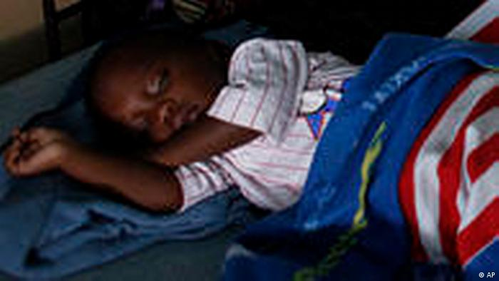 A Kenyan child sleeps under a mosquito net