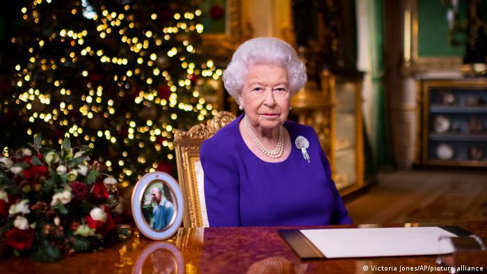 A rainha Elizabeth sentada à mesa, em uma sala decorada de Natal