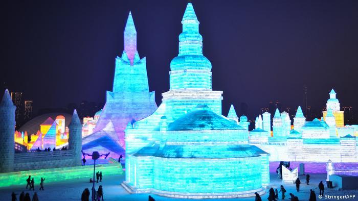 Tourists looking at illuminated ice sculptures at night