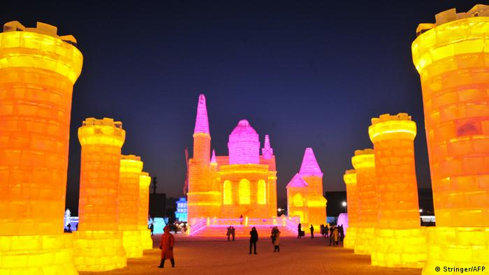 Tourists look at ice sculptures colored with LED lamps