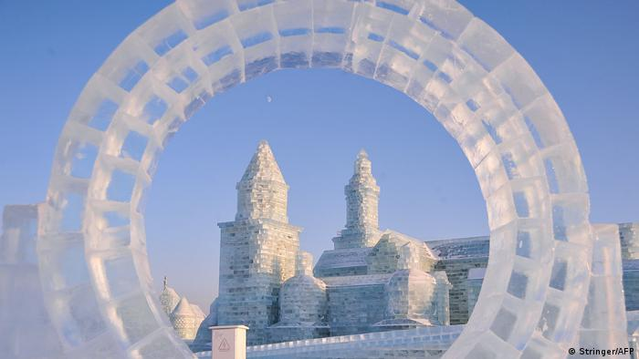 An archway of ice frames an ice castle in the distance