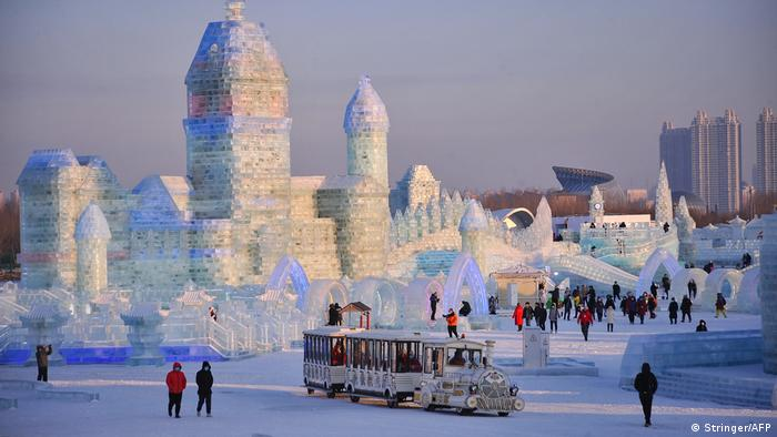 This photo shows tourists looking at a city of ice ahead of the Harbin International Ice and Snow Festival in Harbin