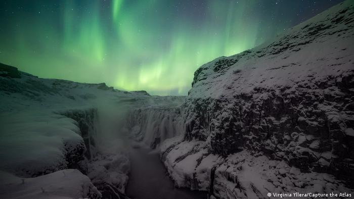Fotografie von Polarlichtern von Virginia Yllera: Ein Wasserfall am Ende eines schneebedeckten Canyons, dahinter ein hell erleuchteter Himmel