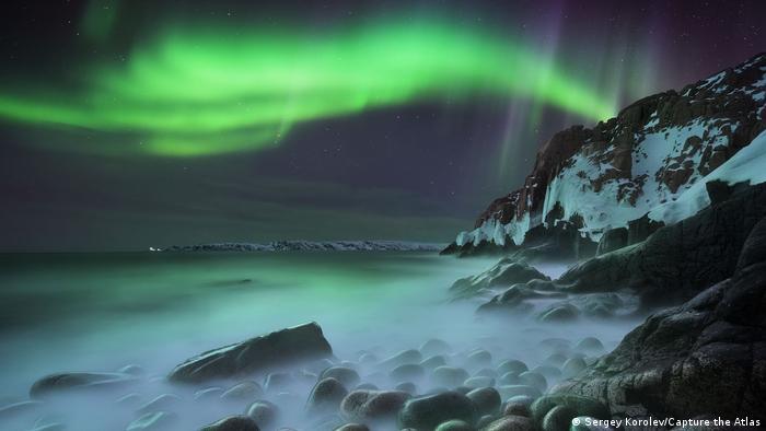 Fotografie von Polarlichtern von Sergej Korolev: Grünes Nordlicht über einem nächtlichen Steinstrand, schneebedeckte Berge im Hintergrund.