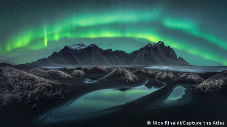 Fotografie von Polarlichtern von Nico Rinaldi: Ein Strand mit schwarzem Sand und Dünen, dahinter ein dunkler Berg, umgeben von einem doppelten Strang hell strahlenden Lichts.