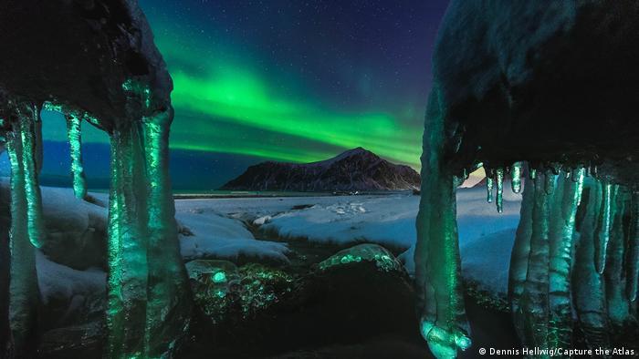 Fotografie von Polarlichtern von Dennis Hellwig: Große Eiszapfen, dahinter eine verschneite Landschaft und ein Berg mit einem hell strahlenden Nordlicht über seiner Spitze.