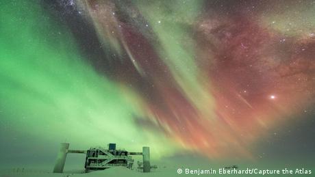 Fotografie von Polarlichtern von Benjamin Eberhardt: Lichtspiel über einer futuristisch geformten Forschungsstation im Eis.