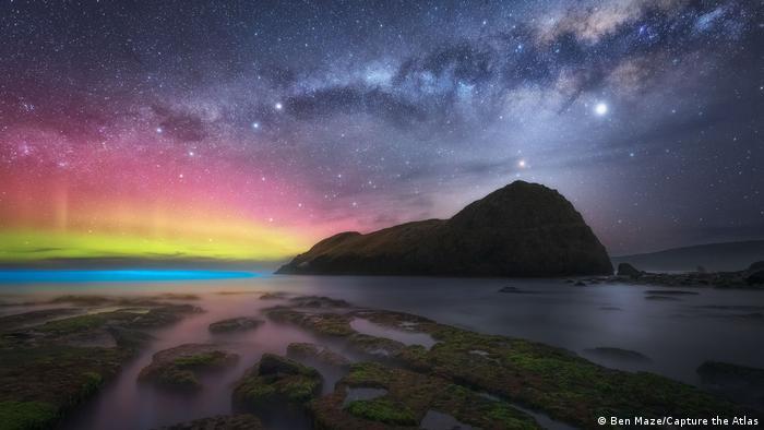Fotografie von Polarlichtern von ben Maze: Verschiedenfarbige Lichtspiele am Horizont, darüber der Sternenhimmel, im Vordergrund ein Strand, im Hintergrund ein großer Felsen am Meer.