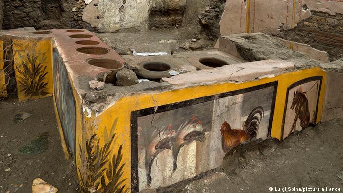 Archäologen haben einen intakten Tresen in einer antiken Imbissbude aus der Zeit des Untergangs der Stadt ausgegraben. Zu sehen ist eine Mauer, auf der verschiedene Tiere abgebildet sind.